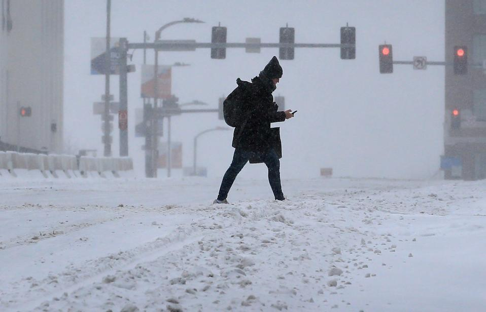 A pedestrian crosses Market Street during a snow storm in downtown St. Louis on Monday, Feb. 15, 2021. The brutally cold weather is expected to continue through Saturday with more snow in the forecast for Wednesday and Thursday. (David Carson/St. Louis Post-Dispatch via AP)