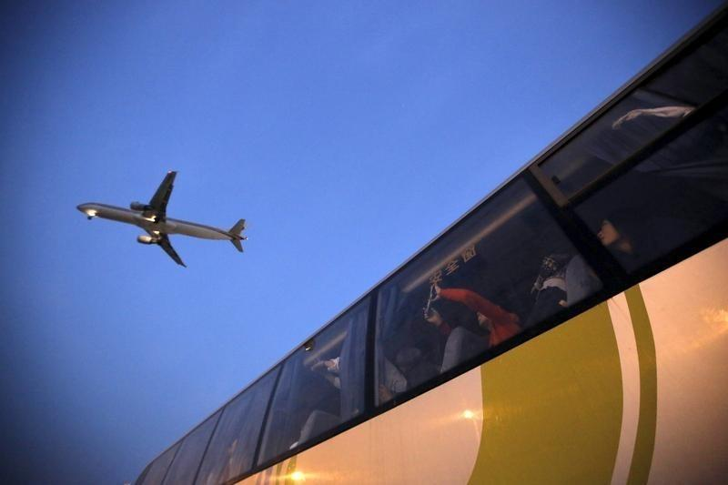 People on a bus look at an airplane as it lands at Hongqiao International Airport in Shanghai