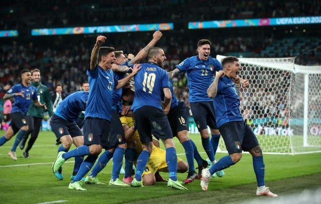 Italy players celebrate winning the penalty shootout