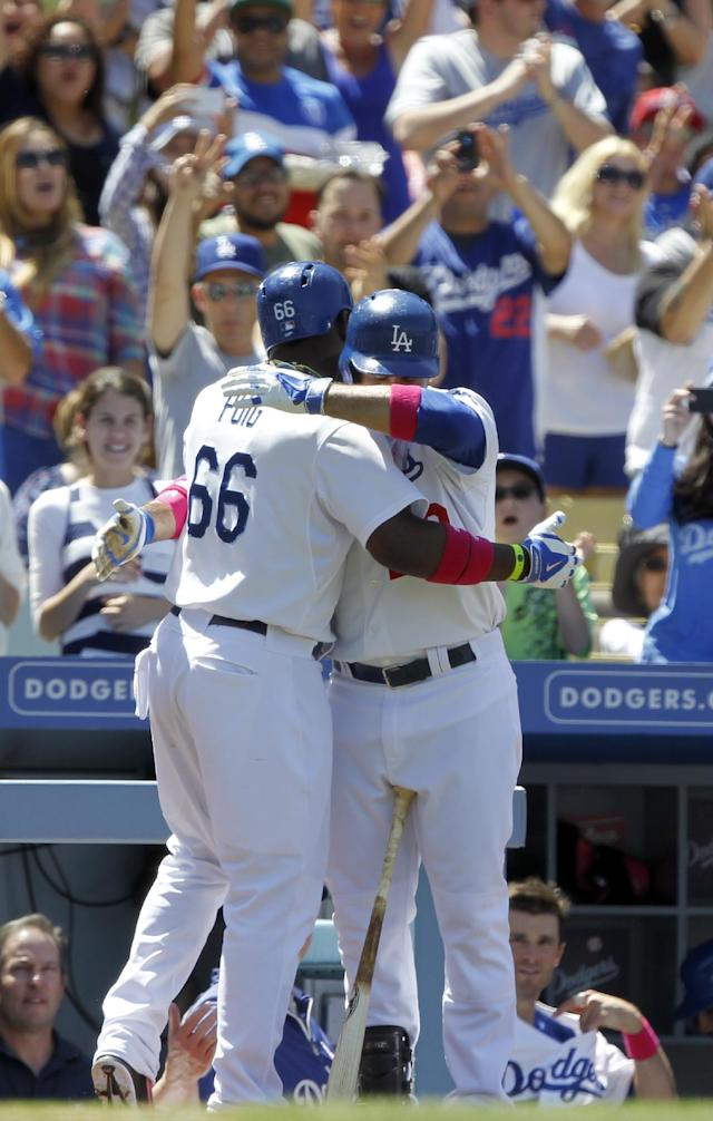 Los Angeles Dodgers' Yasiel Puig (66) gets a hug from Adrian Gonzalez after Puig hit a solo home run against the San Francisco Giants in the sixth inning of a baseball game on Sunday, May 11, 2014, in Los Angeles. (AP Photo/Alex Gallardo)