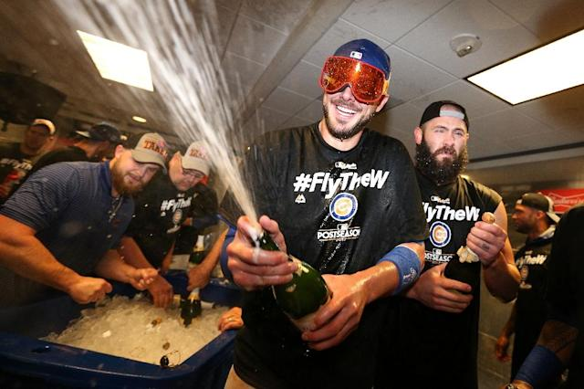 Kris Bryant of the Chicago Cubs celebrates in the clubhouse with teammates after defeating the Washington Nationals 9-8 in game five of the National League Division Series, at Nationals Park in Washington, DC, on October 13, 2017 (AFP Photo/Patrick Smith)