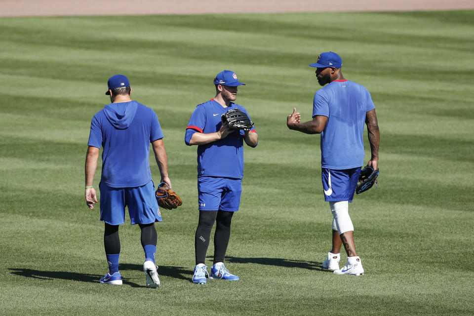 Chicago Cubs right fielder Jason Heyward, right, talks with center fielder Ian Happ, center, and left fielder Kyle Schwarber, left, during baseball practice at Wrigley Field on Friday, July 3, 2020 in Chicago. (AP Photo/Kamil Krzaczynski)