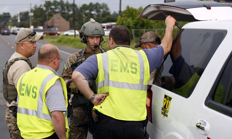 Two federal law officers speak to local EMS technicians along La. Highway 128 outside a Tensas State Bank branch during a hostage situation in St. Joseph, La., Tuesday, Aug. 13, 2013. A man whose family owns a store across the street from the bank took three bank employees hostage, and a state police negotiator has been talking to him for hours, police said. (AP Photo/Rogelio V. Solis)