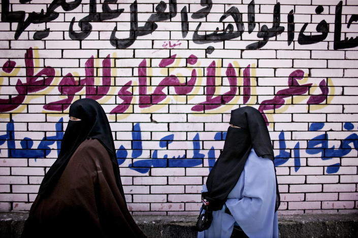 Egyptian women stand in front of graffiti after casting their votes at a polling center in the Mataraya neighborhood of Cairo, Egypt, Thursday, May 24, 2012. In a wide-open race that will define the nation's future political course, Egyptian voted Thursday on the second day of a landmark presidential election that will produce a successor to longtime authoritarian ruler Hosni Mubarak. (AP Photo/Pete Muller)