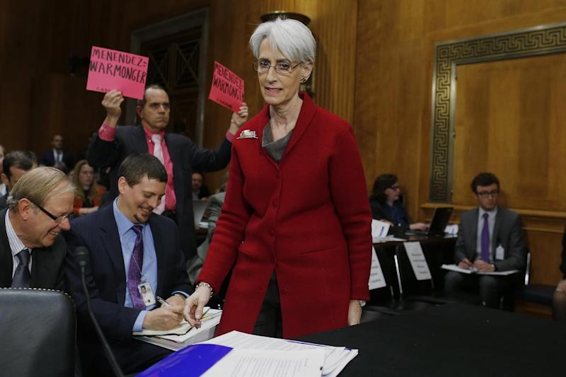 An anti war protestor holds up signs as Undersecretary of State for Political Affairs Wendy Sherman arrives on Capitol Hill in Washington, Tuesday, Feb. 4, 2014, to testify before the Senate Foreign Relations Committee hearing examining negotiations on Iran's nuclear program. (AP Photo/Charles Dharapak)