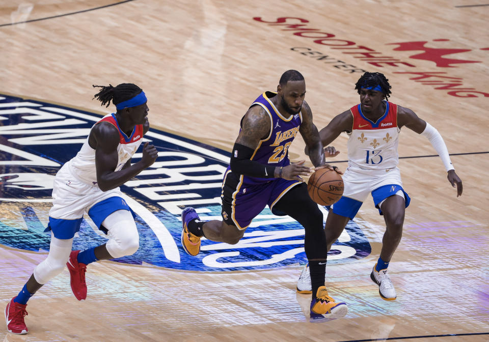 Los Angeles Lakers forward LeBron James (23) drives past New Orleans Pelicans guard Kira Lewis Jr., (13) and forward Wenyen Gabriel (32) in the second quarter of an NBA basketball game in New Orleans, Sunday, May 16, 2021. (AP Photo/Derick Hingle)