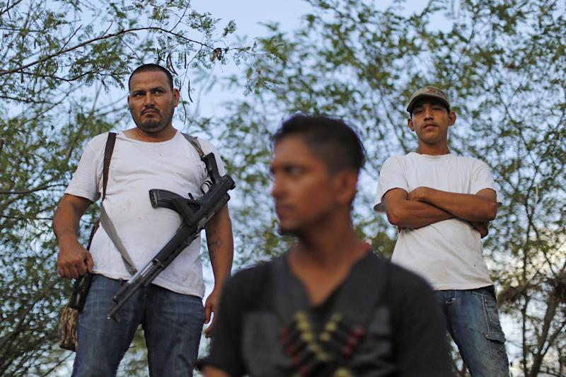 """In this Nov. 5 photo, armed men from to a self-defense group create a checkpoint in the town of Las Colonias, Mexico. Several communities have created their own self-defense groups after a pseudo-religious cartel, known as the """"Knights Templar,"""" has for years demanded protection payments from cattlemen, lime growers and other businesses. The groups say they are free of the cartel in several municipalities of the Tierra Caliente, or """"Hot Land,"""" which earned its moniker for the scorching weather but whose name has also come to signify criminal activity. (AP Photo/Dario Lopez-Mills)"""