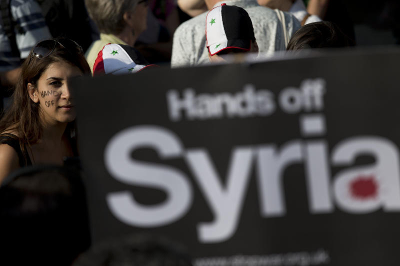 "A woman with the words ""hands off"" painted on her face takes part in a protest organized by the Stop the War coalition calling for no military attack on Syria from the U.S., Britain or France, across the road from the entrance of Downing Street in London, Wednesday, Aug. 28, 2013. Britain said it would seek U.N. Security Council backing Wednesday for a measure condemning Syria for an alleged chemical attack against its civilians and authorizing ""appropriate measures"" in response. The resolution could be used to authorize military force against Syria. (AP Photo/Matt Dunham)"