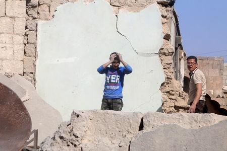 A youth reacts as he stands among the rubble after his father was killed in an airstrike on his home in the rebel-held Old Aleppo, Syria April 16, 2016. REUTERS/Abdalrhman Ismail