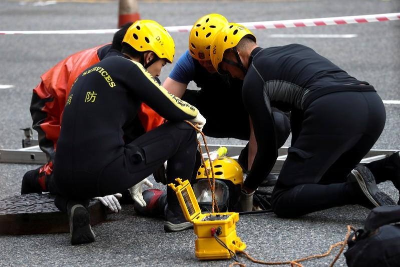 A rescue diver from the Fire Service department enters the sewage system to search anti-government protesters who escaped from the Hong Kong Polytechnic University (PolyU) after being barricaded by police officers
