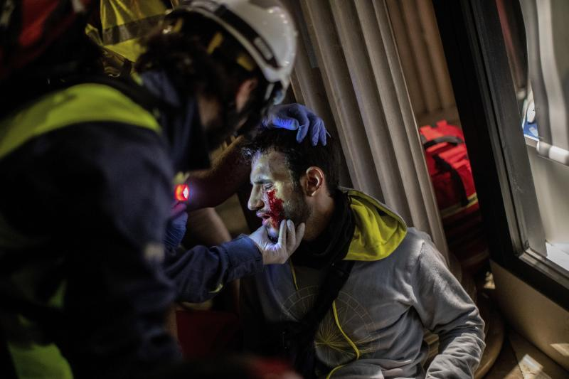 Paramedics attend a protestor during clashes with police in Barcelona, Spain, early Friday, Oct. 18, 2019. (Photo: Bernat Armangue/AP)
