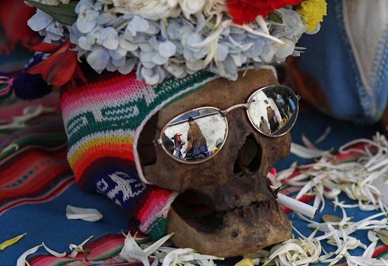 A human skull decorated with sun glasses, a hat and flowers sit on display outside the General Cemetery chapel during the annual 'Natitas' festival in La Pazon 8 November 2019. The celebration blends Christian and traditional indigenous customs.