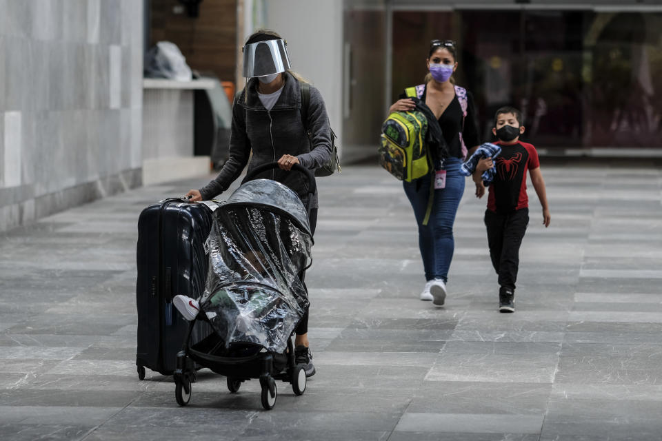Passengers walk through the airport wearing face masks amid the COVID-19 pandemic in Cancun, Mexico, Saturday, June 13, 2020. In Quintana Roo state, where Cancun is located, tourism is the only industry there is, and Cancun is the only major Mexican resort to reopen so far. (AP Photo/Victor Ruiz)