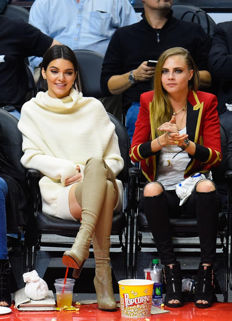 While they're wearing very different looks--Kendall Jenner went full Yeezy monochromatic, while Cara Delevingne channeled a British guard--both supermodels got the memo about heels: when you're courtside, they're a must.