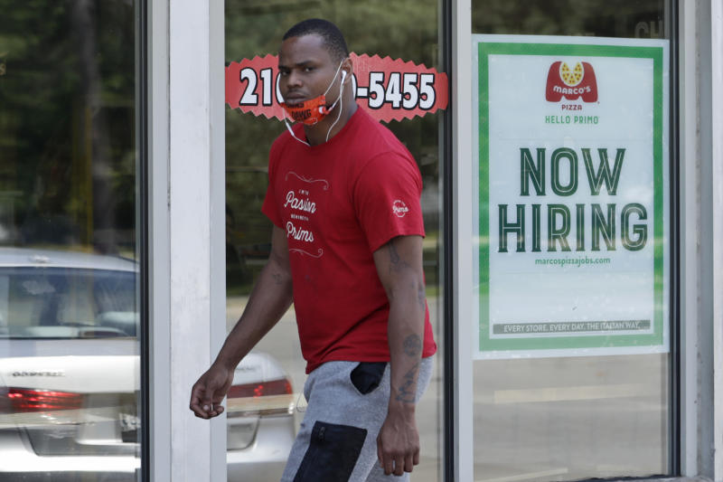 A man walks past Marco's Pizza, which is now hiring, Friday, June 5, 2020, in Euclid, Ohio. U.S. unemployment dropped unexpectedly in May to 13.3% as reopened businesses began recalling millions of workers faster than economists had predicted, triggering a rally Friday on Wall Street. (AP Photo/Tony Dejak)