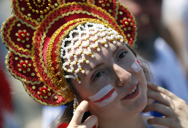 <p>A soccer fan with her face painted in the colours of the England national flag gestures outside the venue </p>