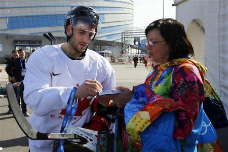 Canada's ice hockey player Patrice Bergeron signs an autograph following a men's team practice at the 2014 Sochi Winter Olympics February 20, 2014. REUTERS/Brian Snyder