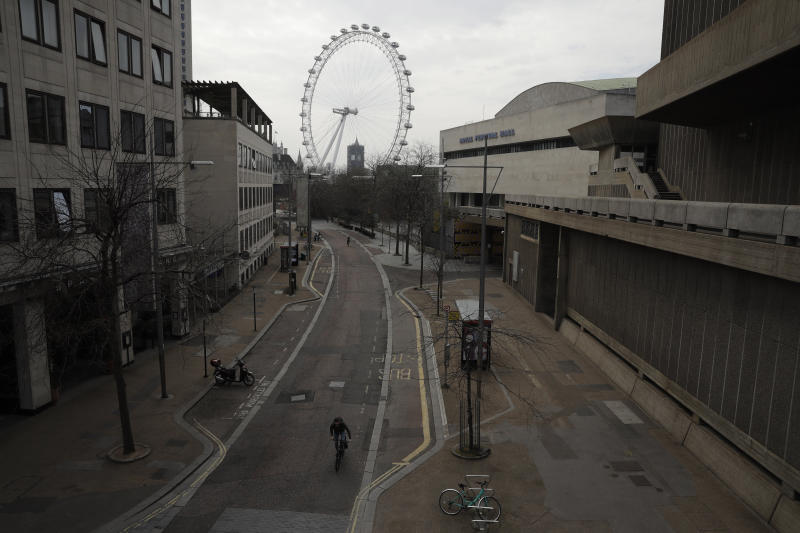 Big Ben's clock tower and the London Eye ferris wheel stand in the distance as the area around Royal Festival Hall is very quiet in London, Wednesday, April 8, 2020. The new coronavirus causes mild or moderate symptoms for most people, but for some, especially older adults and people with existing health problems, it can cause more severe illness or death. (AP Photo/Matt Dunham)