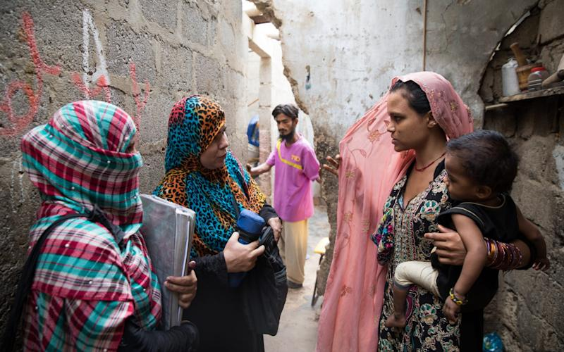 Health workers persuade parents to have their children vaccinated against polio in the back streets of Karachi. Their job is being made more difficult by fake news - Insiya Syed