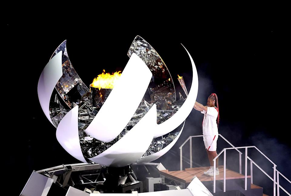 Naomi Osaka of Team Japan lights the Olympic cauldron with the Olympic torch during the opening ceremony.