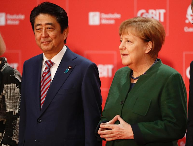 German Chancellor Angela Merkel (R) arrives with Japanese Prime Minister Shinzo Abe at the official opening of the CeBIT technology fair in Hanover on March 19, 2017
