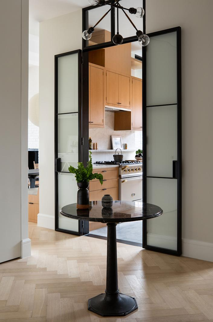 "<div class=""caption""> ""The jewel-box kitchen, which showcases floor-to-ceiling oak cabinetry and is framed by steel casement doors,"" says Gabriela. ""This achieves the open-and-closed kitchen concept seamlessly."" The pendant is by <a href=""https://apparatusstudio.com/product-category/lighting/ceiling/"" rel=""nofollow noopener"" target=""_blank"" data-ylk=""slk:Apparatus Studio"" class=""link rapid-noclick-resp"">Apparatus Studio</a>, and the vintage table is from <a href=""https://www.cityfoundry.com/"" rel=""nofollow noopener"" target=""_blank"" data-ylk=""slk:City Foundry"" class=""link rapid-noclick-resp"">City Foundry</a>. </div>"