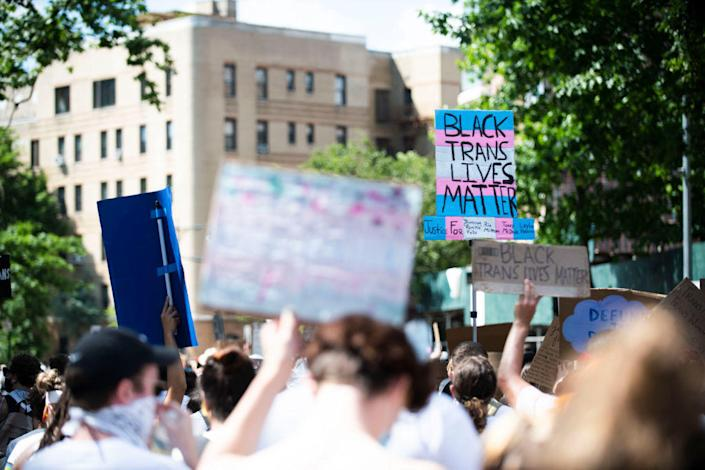 Protestors march with chants, flags, sign and white clothing in support of Black Trans Lives Matter on June 14, 2020. / Credit: Michael Noble Jr. / Getty Images