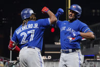 Toronto Blue Jays Marcus Semien, right, celebrates his solo home run off Minnesota Twins pitcher Bailey Ober with Vladimir Guerrero Jr. in the sixth inning of a baseball game, Friday, Sept. 24, 2021, in Minneapolis. (AP Photo/Jim Mone)