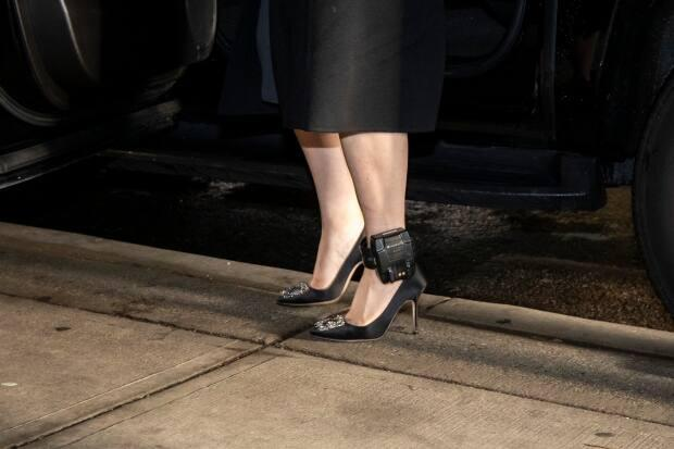 Huawei chief financial officer Meng Wanzhou displays her GPS ankle monitoring bracelet as she arrives at B.C. Supreme Court in Vancouver. She is living under a form of house arrest.