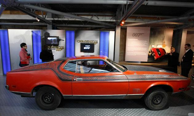 "Visitors look at the Ford Mustang Mach 1, featured in the 1971 James Bond film ""Diamonds Are Forever"" on display during the opening of a press preview of the Bond in Motion exhibition at the Beaulieu National Motor Museum at Brockenhurst in the southern English county of Hampshire on January 15, 2012. The Bond in Motion exhbition features fifty original iconic vehicles used in the James Bond films to celebrate fifty years of 007 and will open to the public from January 17. AFP PHOTO / JUSTIN TALLIS"