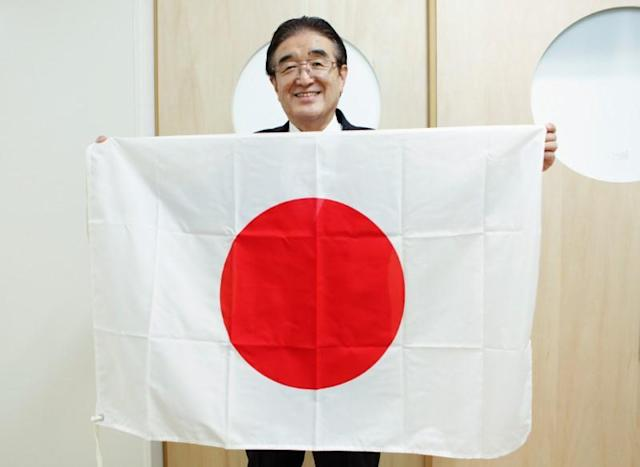 Tadamasa Fukiura, flag supervisor and consultant to Tokyo 2020 Olympic and Paralympic Games organisers, holds a Japanese national flag