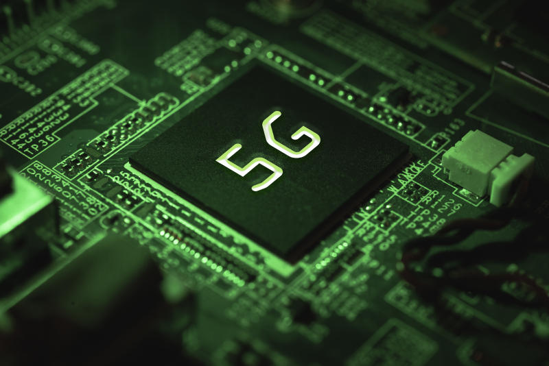 Motherboard with 5g chip and green artificial light. Communication, data and tech concept.