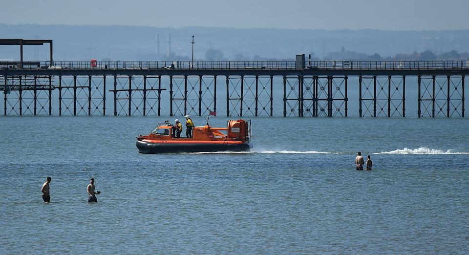 Members of the RNLI (Royal National Lifeboat Institution) patrol the water on a hovercraft as beachgoers enjoy the sunshine on the beach and in the sea on the May Bank holiday, in Southend-on-Sea, south east England on May 25, 2020, after lockdown restrictions, originally put in place due the COVID-19 pandemic, were lifted earlier this month. - British Prime Minister Boris Johnson on Sunday backed top aide Dominic Cummings despite mounting pressure from within his own party to sack him over claims he broke coronavirus lockdown regulations. (Photo by Ben STANSALL / AFP) (Photo by BEN STANSALL/AFP via Getty Images)