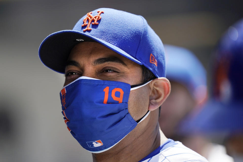 New York Mets manager Luis Rojas (19) appears to smile beneath his mask between innings of the Mets 7-1 victory over the Baltimore Orioles in a baseball game, Wednesday, May 12, 2021, in New York. The Mets swept the Orioles in a two-game series. (AP Photo/Kathy Willens)