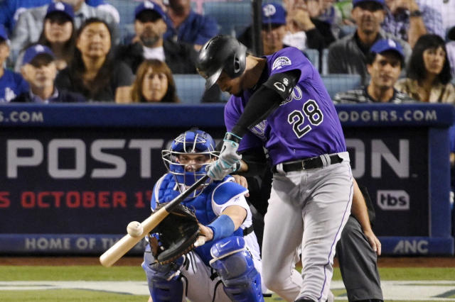 Colorado Rockies' Nolan Arenado hits a solo home run in front of Los Angeles Dodgers catcher Will Smith during the first inning of a baseball game Friday, Sept. 20, 2019, in Los Angeles. (AP Photo/Mark J. Terrill)