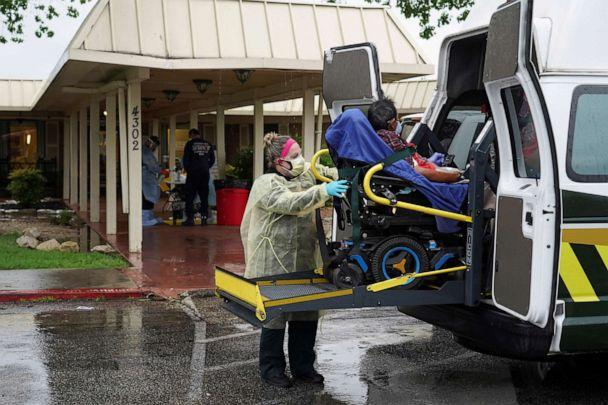 PHOTO: A healthcare worker in a protective suits helps an elderly person to get off an ambulance on April 4, 2020. (Go Nakamura/Reuters)
