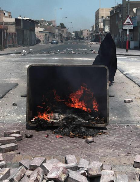 A Bahraini woman walks on a closed road with burning debris and closed stores and businesses in the western village of Malkiya, Bahrain, Wednesday, Aug. 14, 2013. Opposition groups launched a fresh push against the Gulf monarchy on Wednesday, an effort to revitalize their two-and-a half-year-old pro-democracy uprising. (AP Photo/Hasan Jamali)