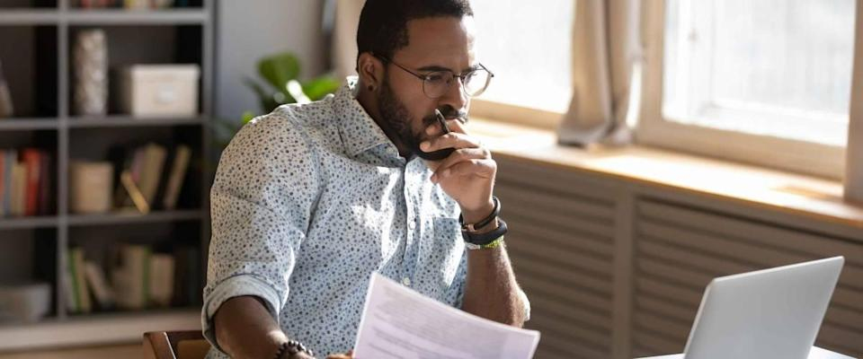 Focused African-American man holding paper and looking at laptop computer
