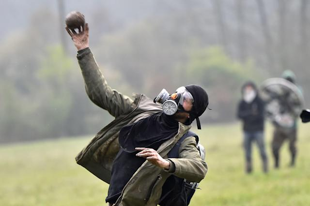 <p>A protester hurls stone toward riot forces on April 10, 2018 on the second day of a police operation to raze the decade-old camp known as ZAD (Zone a Defendre – Zone to defend) at Notre-Dame-des-Landes, near the western city of Nantes, and evict the last of the protesters who had refused to leave despite the government agreeing to ditch a proposed airport. (Photo: Loic Venance/AFP/Getty Images) </p>