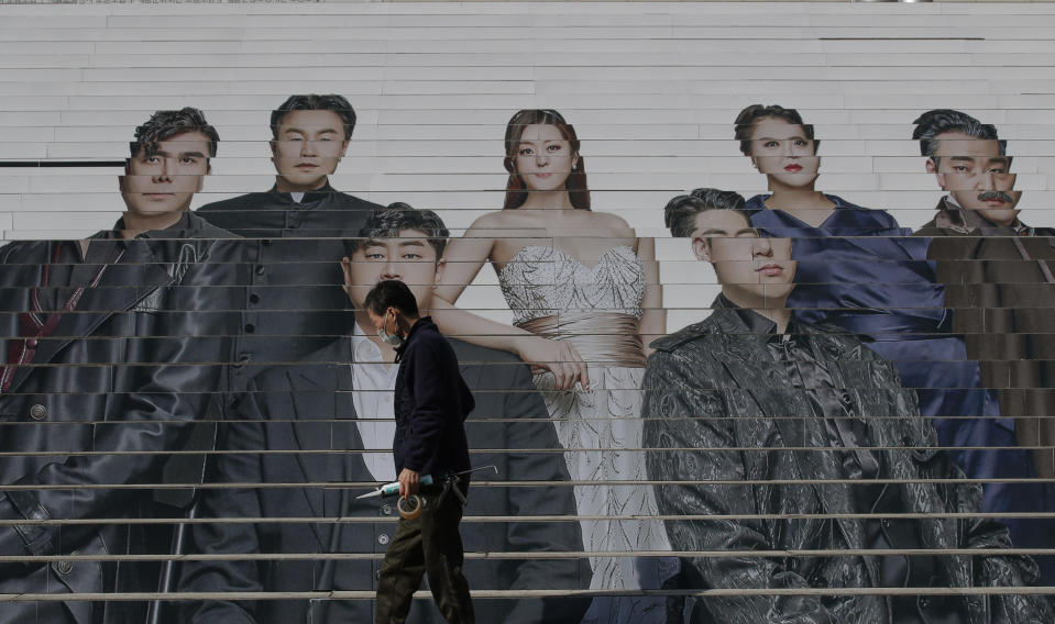 A man wearing a face mask as a precaution against the coronavirus, walks past in front of an advertisement of an opera performance outside of a theater in Seoul, South Korea, Wednesday, March 3, 2021. (AP Photo/Lee Jin-man)