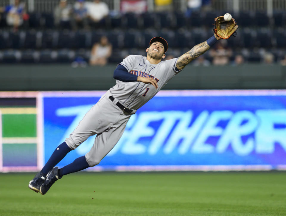 Houston Astros shortstop Carlos Correa can't quite reach a single by Kansas City Royals' Andrew Benintendi during the fourth inning of a baseball game Tuesday, Aug. 17, 2021, in Kansas City, Mo. (AP Photo/Reed Hoffmann)