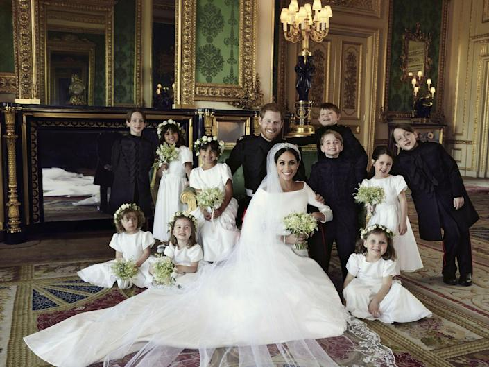 """<p>In <a href=""""https://www.townandcountrymag.com/society/tradition/a20747996/meghan-markle-prince-harry-kate-middleton-official-royal-wedding-portraits-comparison/"""" rel=""""nofollow noopener"""" target=""""_blank"""" data-ylk=""""slk:an official royal wedding portrait taken by Alexi Lubomirski"""" class=""""link rapid-noclick-resp"""">an official royal wedding portrait taken by Alexi Lubomirski</a>, Prince Harry and Meghan Markle pose with their page boys and bridesmaids, including a very smiley Prince George.</p>"""