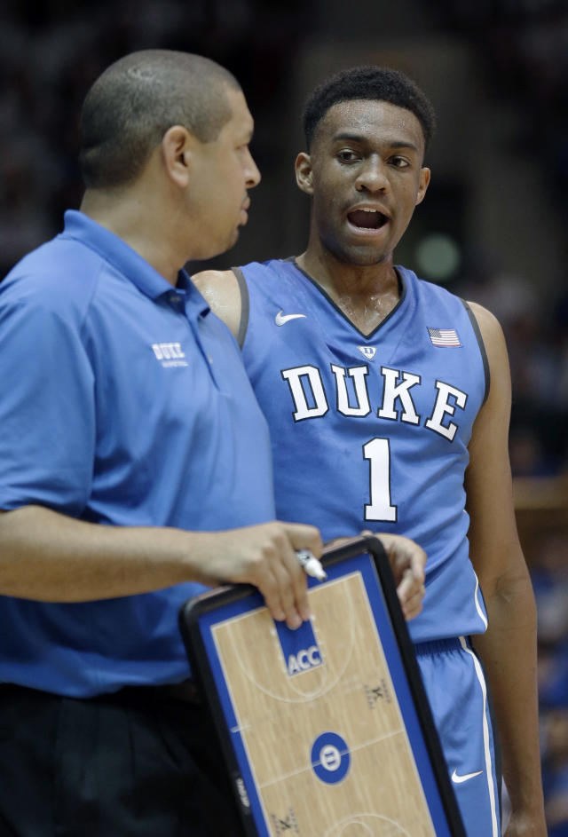 Duke's Jabari Parker (1) speaks with assistant coach Jeff Capel during the team's Countdown to Craziness NCAA college basketball preseason event in Durham, N.C., Friday, Oct. 18, 2013. (AP Photo/Gerry Broome)