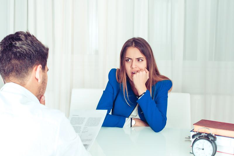 Young nervous woman watching adult man reading paper document of resume at table in office. Anonymous man reading paperwork cv, contract female candidate for vacancy biting fist in stress and worries.