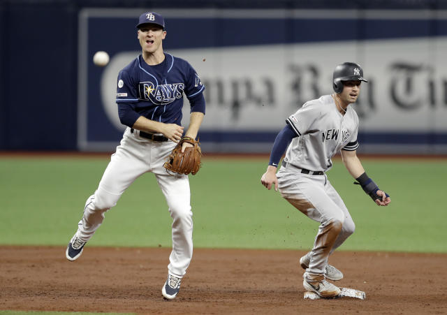 Tampa Bay Rays' Joey Wendle throws to first after forcing out New York Yankees' Tyler Wade, right, at second base, for a double play on DJ LeMahieu during the third inning of a baseball game Wednesday, Sept. 25, 2019, in St. Petersburg, Fla. (AP Photo/Chris O'Meara)