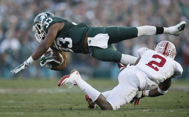 Michigan State running back Jeremy Langford, top, makes a gain against Stanford cornerback Wayne Lyon during the second half of the Rose Bowl NCAA college football game Wednesday, Jan. 1, 2014, in Pasadena, Calif. (AP Photo/Danny Moloshok)