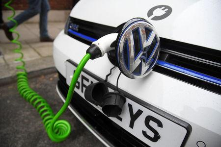 FILE PHOTO: An electric Volkswagen car is plugged into a recharging point in central London