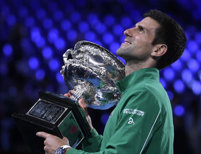 Serbia's Novak Djokovic holds the Norman Brookes Challenge Cup after defeating Austria's Dominic Thiem in the final of the Australian Open tennis championship in Melbourne, Australia, Monday, Feb. 3, 2020. (AP Photo/Andy Brownbill)