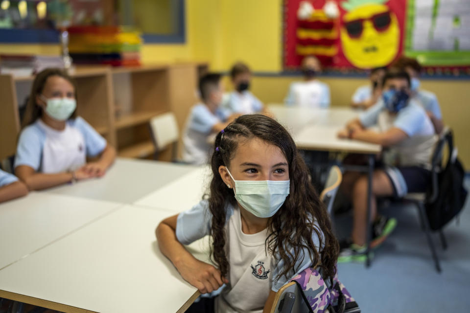 Pupils wearing a face mask to protect against the spread of coronavirus attend a class at Maestro Padilla school as the new school year begins, in Madrid, Spain, Tuesday, Sept. 7, 2021. Around 8 million children in Spain are set to start the new school year. (AP Photo/Manu Fernandez)