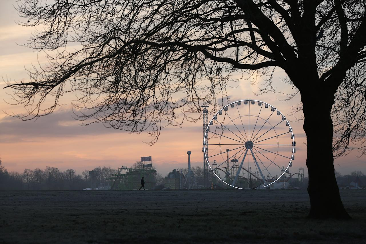 LONDON, UNITED KINGDOM - DECEMBER 12:  Members of the public walk through the early morning frost in Hyde Park on December 12, 2012 in London, England. Forecasters have warned that the UK could experience the coldest day of the year so far today, with temperatures dropping as low as -14C, bringing widespread ice, harsh frosts and freezing fog. Travel disruption is expected with warnings for heavy snow in some parts of the country.  (Photo by Oli Scarff/Getty Images)